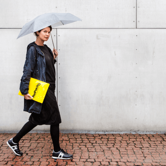 Woman walking in rain with umbrella and RePack bag under her arm